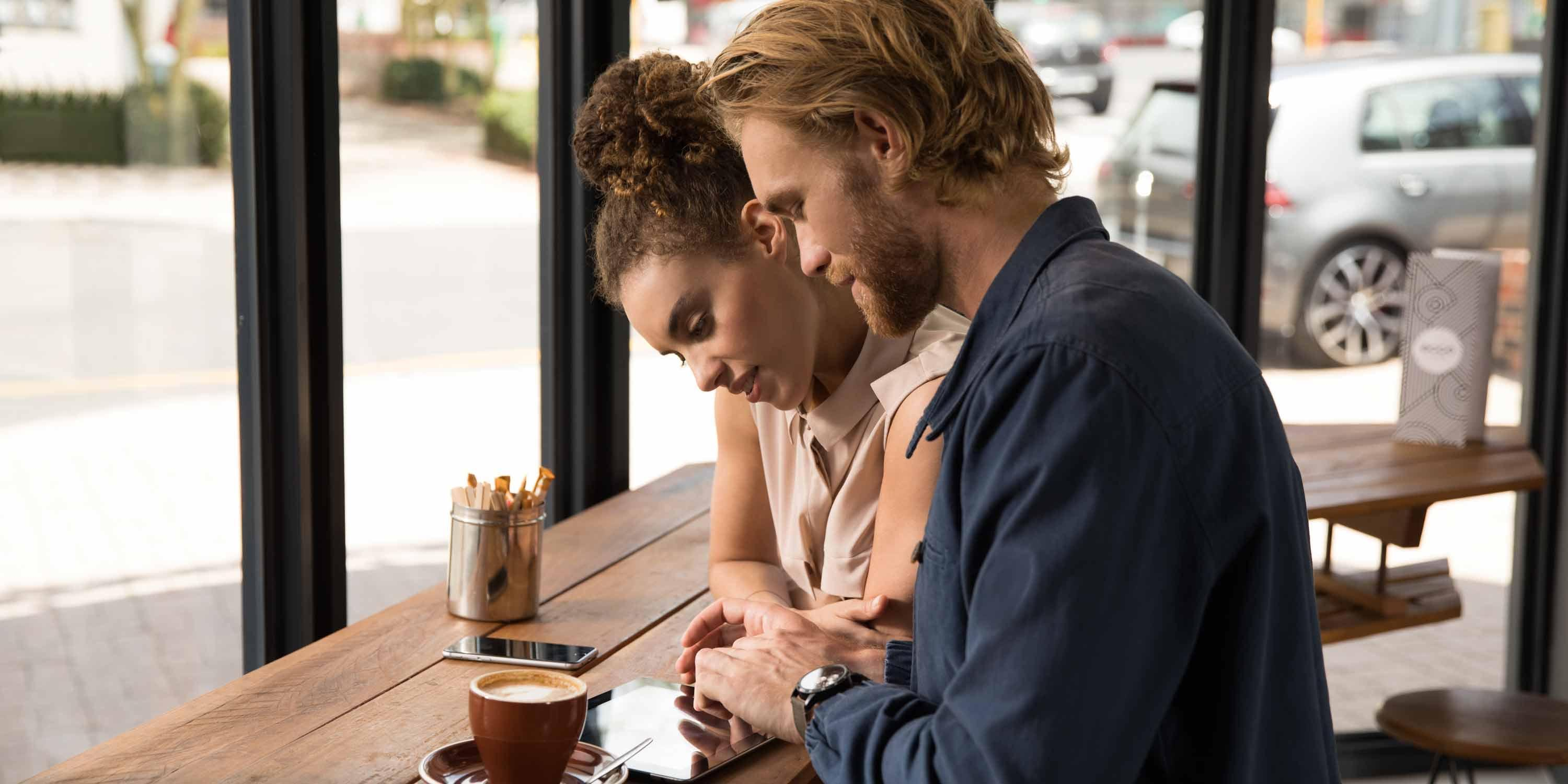 couple-in-cafe-looks-on-tablet